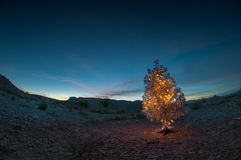 Christmas Tree in the Desert. A silver metallic Christmas tree with lights in the west Texas desert Stock Image