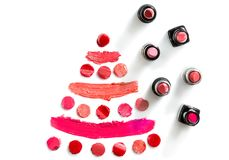 Lipstick on white background top view. Christmas tree of different color slices of lipsticks and stickers nearby Stock Image