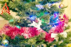 Christmas tree with different toys, decorations and garlands. In a room Stock Photo