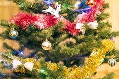 Christmas tree with different toys, decorations and garlands. In a room Stock Images