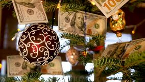 Christmas tree with dollars. The dollars are hanging on the Christmas tree stock video