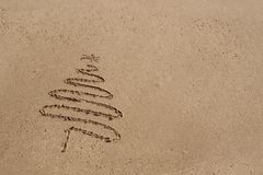 Christmas tree drawn in sand at the beach.  royalty free stock photography