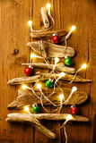 Christmas tree from Dry sticks with garlands and balls Royalty Free Stock Photos