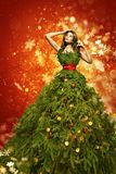 Christmas Tree Fashion Dress, Woman Art Xmas Gown, New Year Girl. Christmas Tree Fashion Dress, Woman in Art Xmas Gown, New Year Girl posing over red lighting Royalty Free Stock Photos