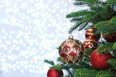 Christmas tree with festive decor against fairy lights royalty free stock photo