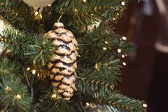 Christmas tree with festive golden cones and lights with copy space on blurred bokeh background in mall. Xmas card. Stock Images