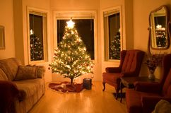 Christmas Tree with few gifts. Fake Christmas tree illuminating a room on Christmas eve Royalty Free Stock Image