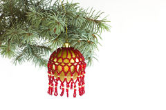 Christmas tree fir branch with hanging handmade craft new year toy ball pattern from red beads Stock Images