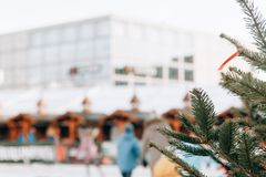 Christmas tree or fir branches in the foreground. The skating rink in Berlin in Alexanderplatz is blurred in the. Background. Christmas Holidays. People relax royalty free stock images