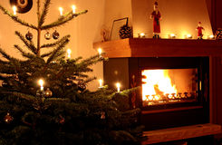 Christmas tree and fire. Christmas tree with lighted decorations next to burning fire in domestic home, festive scene royalty free stock photo