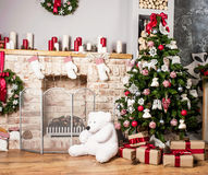 Christmas tree and fire-place. Toy bear, candles and gifts royalty free stock photography