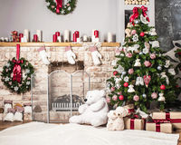 Christmas tree and fire-place. Toy bear, candles and gifts stock images