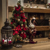 Christmas tree by a fireplace and candles Royalty Free Stock Images
