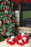 Christmas tree, fireplace and a red gift boxes Royalty Free Stock Images