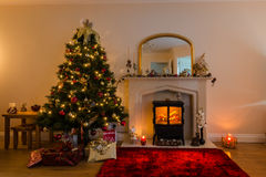 Christmas Tree and Fireplace. Warm glow of Christmas lights and a log burner in festive decoration royalty free stock image