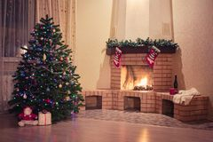 Christmas tree at fireplace with wine bottle. Beautifully decorated christmas tree standing at fireplace in living room of big house with wine bottle, mug and stock photo