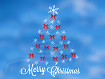 Christmas tree flakes red ribbons card. Christmas tree with flakes and red ribbons greeting card on blue cloudy sky Royalty Free Stock Photography