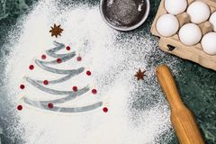 Christmas tree with the flour, berries and anise star spices as a decoration and rolling pin, eggs, strainer Stock Image