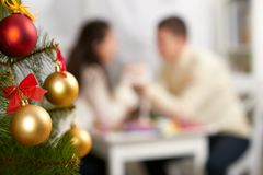 Christmas tree on foreground with defocused romantic young couple sit at the table, happy people and love concept, new year holida. Y Royalty Free Stock Image