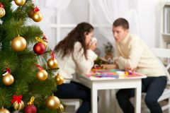 Christmas tree on foreground with defocused romantic young couple sit at the table, happy people and love concept, new year holida Royalty Free Stock Images
