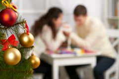 Christmas tree on foreground with defocused romantic young couple sit at the table, happy people and love concept, new year holida. Y Stock Photo