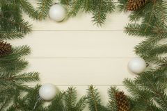 Christmas tree frame branches and balls on wooden background with copy space. Horizontal template for design. Christmas tree frame branches and white balls on stock images