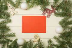Christmas tree frame branches, red envelope, balls and christmas toys on wooden background with copy space. Horizontal template fo. Christmas tree frame branches stock photo