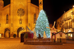 Christmas tree in front of cathedral. Alba, Italy. Big illuminated Christmas tree on central square and San Lorenzo cathedral on background at evening in Alba Stock Images