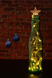 Christmas tree with a garland as a green bottle on the background wall. Stock Images
