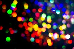 Christmas tree garland light. Colorful bokeh blurry decor on black background. Holiday wallpaper night glowing