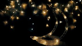 The Christmas tree garland shimmers like the night sky. The moon will rise soon