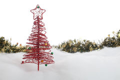 Christmas tree and garland in the snow Royalty Free Stock Photos