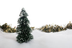 Christmas tree and garland in the snow Stock Images