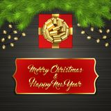 Christmas tree, gift box, bow, garland, label. Christmas card with Cristmas fir tree branches, red square gift box with gold ribbon bow, garland on black wooden Royalty Free Stock Photography