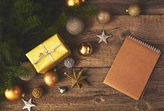 Christmas tree with gift box, decorations and notebook over wood stock images