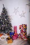 Christmas tree with gift boxes and decorative elements in the room. Gift packages of different colors stock photography