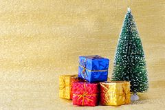 Christmas tree and gift boxes on golden background Royalty Free Stock Photos