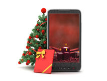 Christmas tree, gift and cell phone. On white background Royalty Free Stock Images