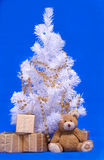 Christmas tree, gifts box and teddi bear. On blue background Stock Photo