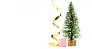 Christmas tree with gifts boxes paking with a bow on a holiday. Christmas tree with a golden serpentine ribbon with gifts boxes paking on a holiday in winter in royalty free stock images