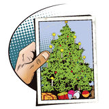 Christmas tree with gifts. Hand with photo. Stock Photo
