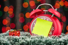 Christmas tree, gifts, lights and alarm clock on abstract backgr Royalty Free Stock Photo