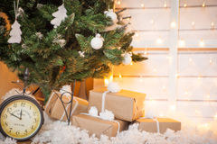Christmas tree with gifts. Old clock, holiday lights Royalty Free Stock Photo