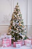 Christmas tree with gifts under it. In a classic bright rich interior Stock Photos