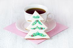 Christmas tree gingerbread with coffe cup on wooden table with pink napkin. Christmas tree gingerbread with coffe cup on wooden table and pink napkin Royalty Free Stock Photo