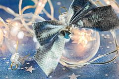 Christmas tree glass balls with silver bow on blue glitter backg Royalty Free Stock Photography