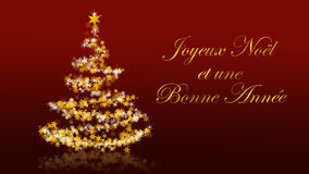 Christmas tree with glittering stars on red background, french seasons greetings. Christmas tree with glittering stars on red background with seasons greetings Stock Image