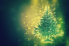 Christmas tree on the glow glitter background. Elegant abstract background with bokeh royalty free stock photos