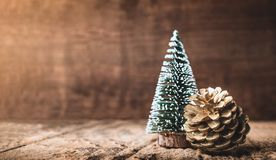 Christmas tree and gold pine cone on grunge wood table and dark brown wooden wall.Winter Merry Christmas holiday greeting card royalty free stock images