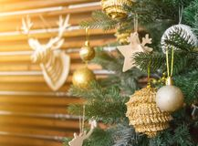 Christmas tree with golden balls, decorations. Deer head model on the wall. New Year concept. Sun shining orange toned stock photo
